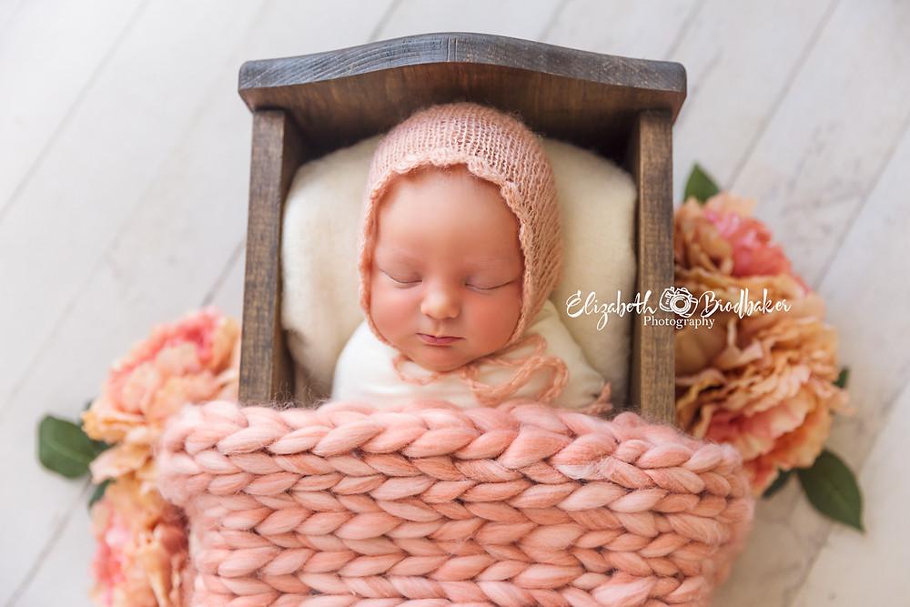 newborn picture in mini bed