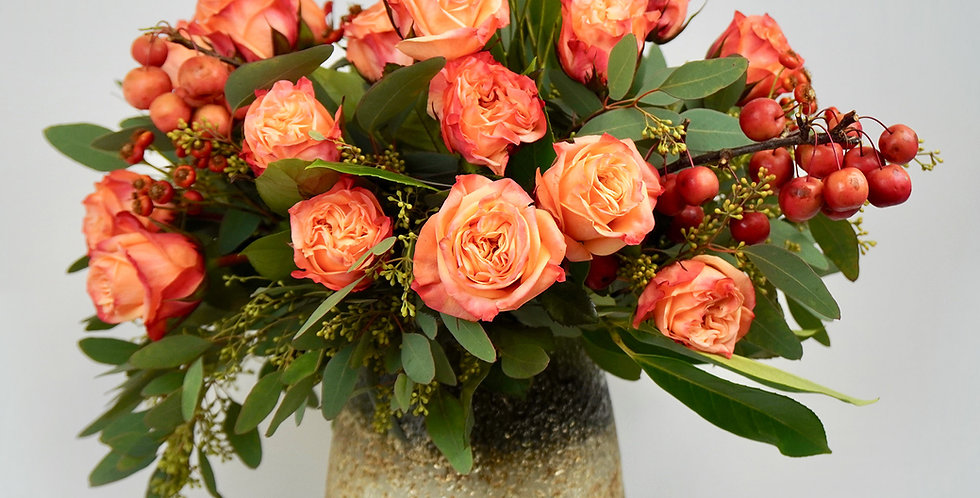 17 roses and matching foliage in an earthy-golden glass vase