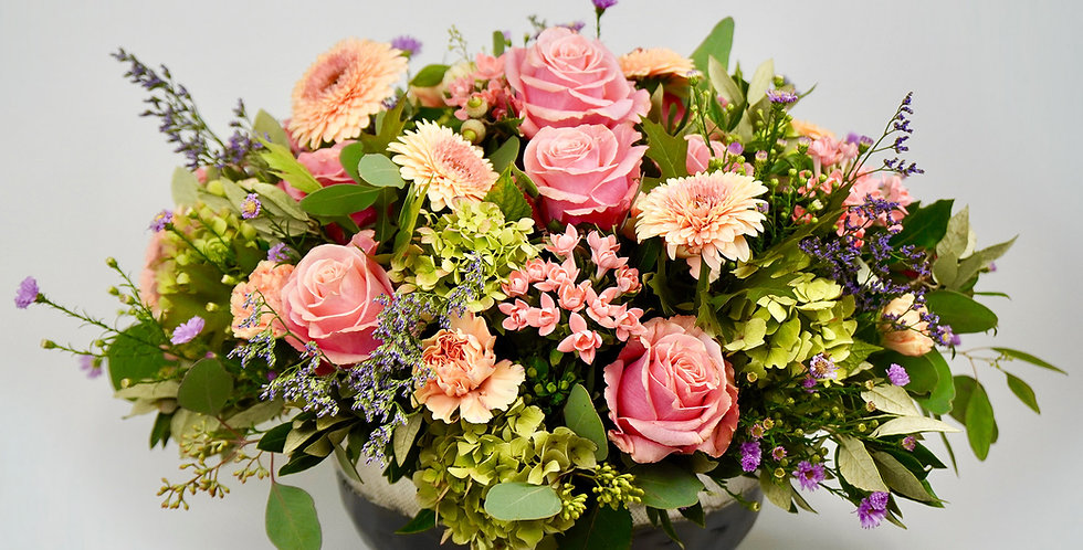 A generous, classic arrangement of flowers and green foliage in a metal bowl