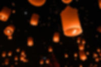 Paper lanterns floating in the starry night sky
