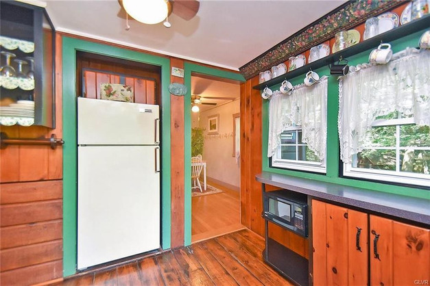 Fireside Pines Kitchen with large refrigerator, microwave, crockpot, coffee maker, toaster, pots and pans, cups, and mugs