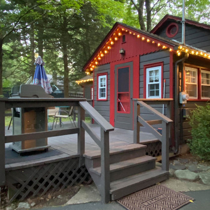 Fireside Pines front entrance with large wood deck, with large table and Weber propane grill