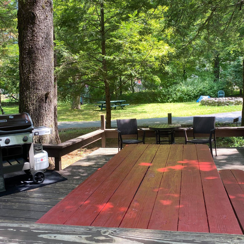 Bear Claw Cabin Deck with Large Picnic Table, Seating Area, and Weber Propane Grill