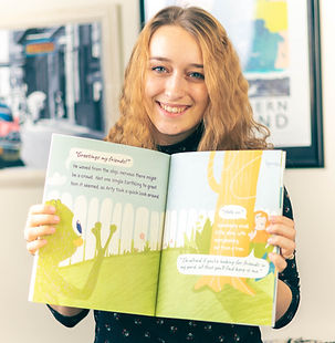 person holding up their book illustrated and published by Inkling