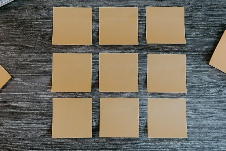Nine sticky notes are pictured on a brown desk.