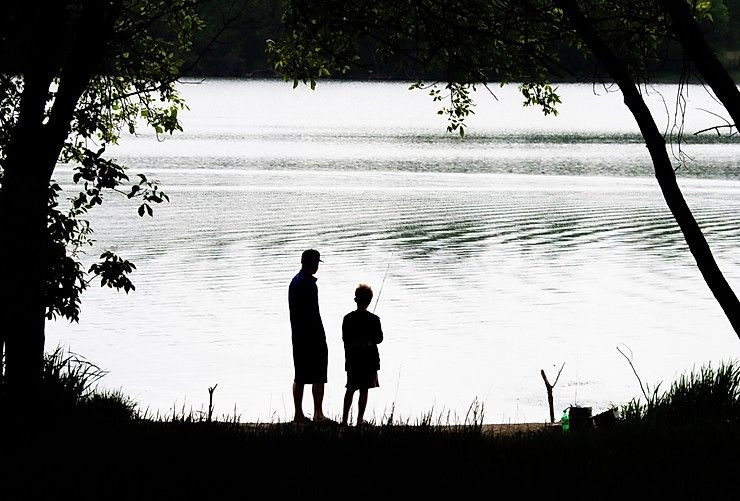 A dad and his child looking out at the lake.