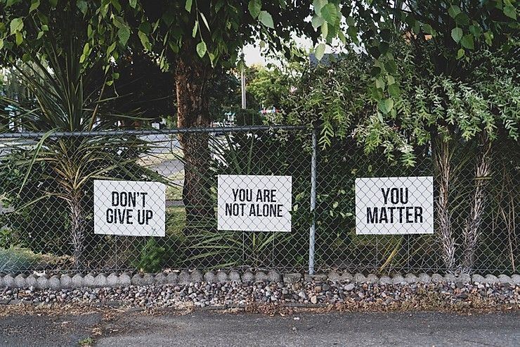 "Signs on a fence that say ""Don't give up,"" ""You are not alone,"" and ""You matter"""