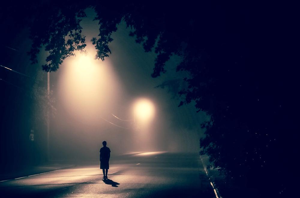 A grieving teen walks down a dark street, alone.