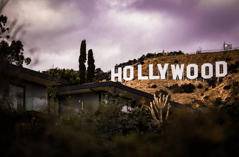 "The ""Hollywood"" sign is pictured with a dark sky and background."