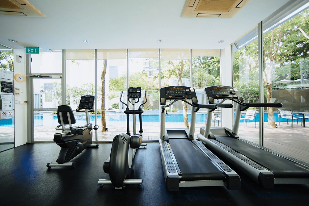 A gym with two treadmills and other exercise machines by a pool are pictured.