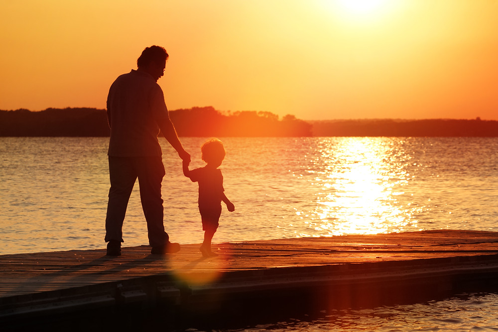 man walking with kid on the beach at sunset