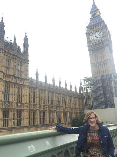 Photo of Claire, in London, just outside the Big Ben. The clock reads near 4:30 pm.