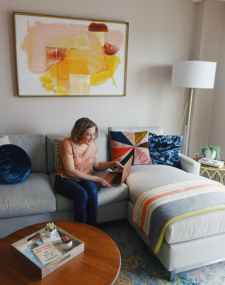 Claire, seated on a couch, holding her computer