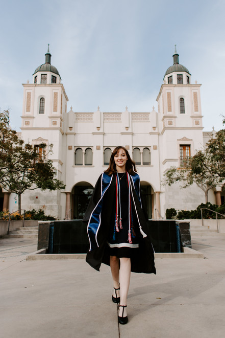 graduate in gown and blue sash walking away from reflecting pool at University of San Diego