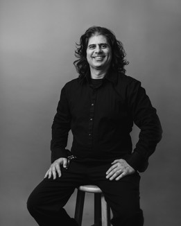 black and white, man in all black with long curly hair sitting on a wooden stool for corporate headshot