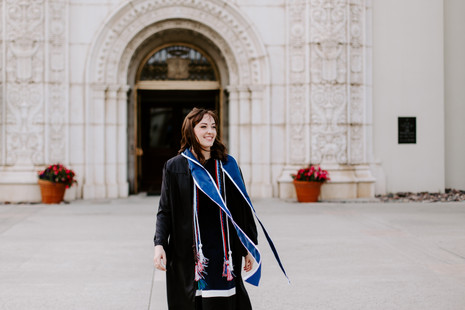 graduate in gown and blue sash blowing in the wind standing in front of chapel at University of San Diego