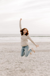 young girl in white sweater and blue jeans jumping at the beach with hands in the air