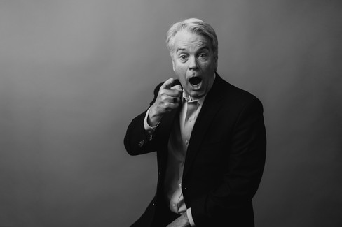 older man with white hair in a suit being silly pointing at camera with open mouth