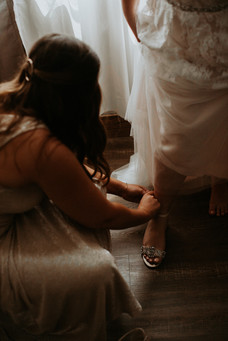 Maid of honor bent down adjusting bride's shoes