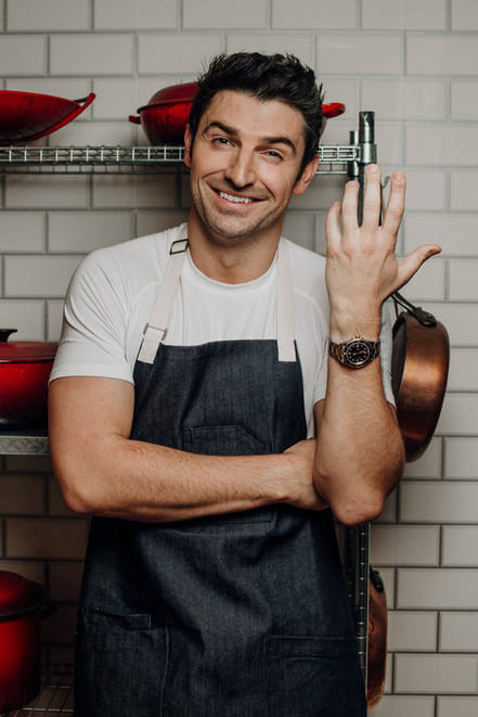 Chef Stuart O'Keeffe in blue apron smiling and laughing in front of subway tile wall