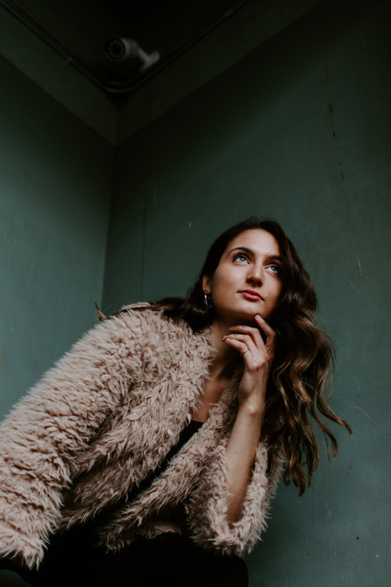 girl with long brown hair and faux fur coat standing by a green wall