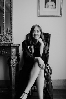black and white, graduate in gown and sash sitting in chair with her legs crossed and resting hand on her chin