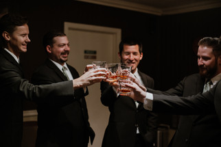 groomsmen getting ready and toasting with glasses of scotch