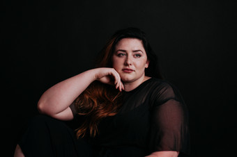 plus-sized model in black lace with dark hair sitting in photo studio with arm on her knee and hand under her face
