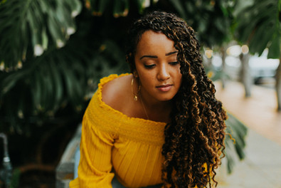 young black woman with locks and yellow top looking at the ground