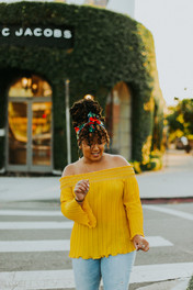 young black woman in yellow top with headwrap dancing