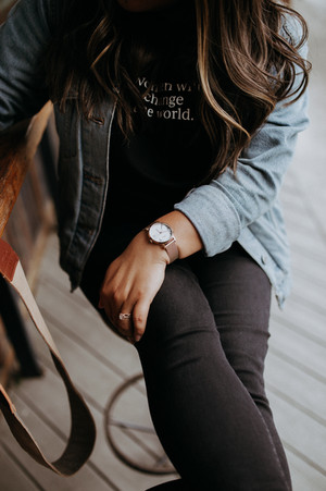 closeup of women's watch with black skinny jeans and denim shirt