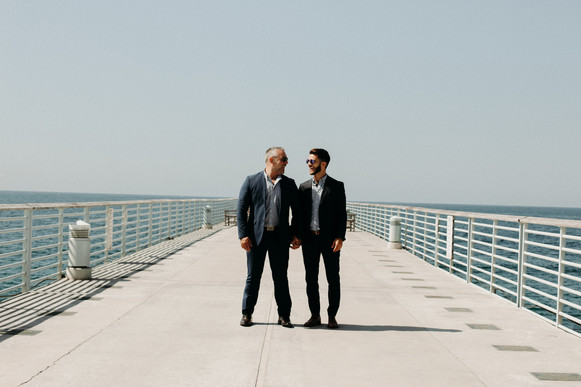two grooms in navy blue suits holding hands in the middle of Hermosa Beach pier
