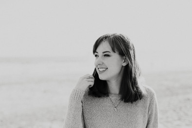 black and white, girl in sweater with short hair and bangs smiling at the beach