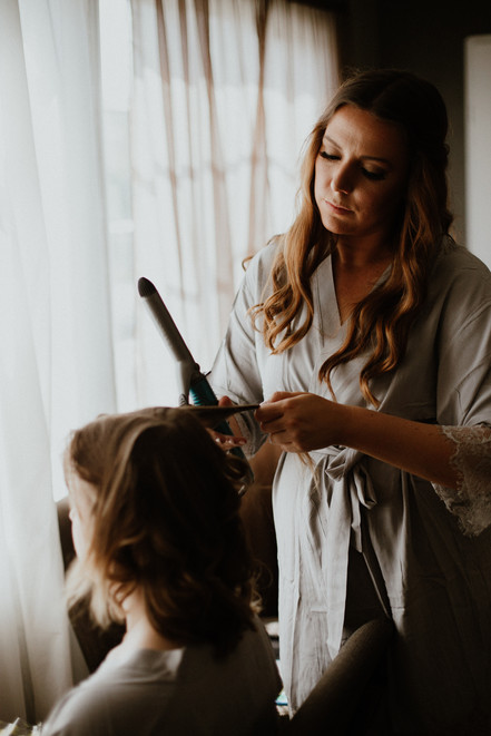 maid of honor by a window curling another bridesmaid's hair