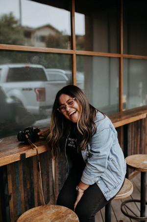 photographer laughing with her camera sitting on a cafe stool
