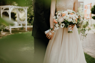 bride in champagne wedding dress holding bouquet of roses and anemones