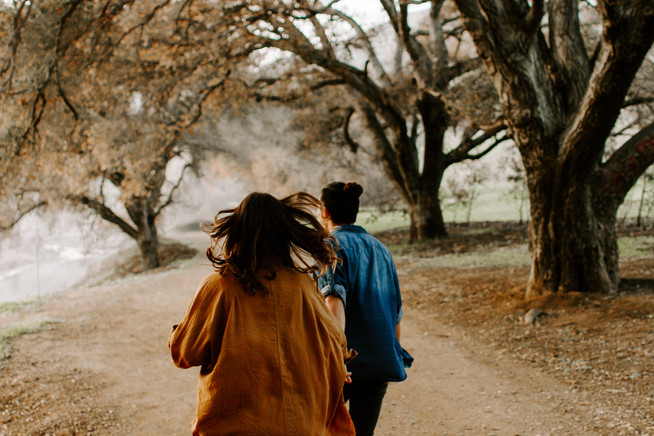 couple in orange blouse and denim shirt running down wooded trail