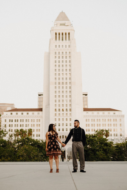 couple holding hands in front of Los Angeles City Hall