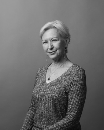 elegant older woman with white hair and sweater posing for corporate headshot