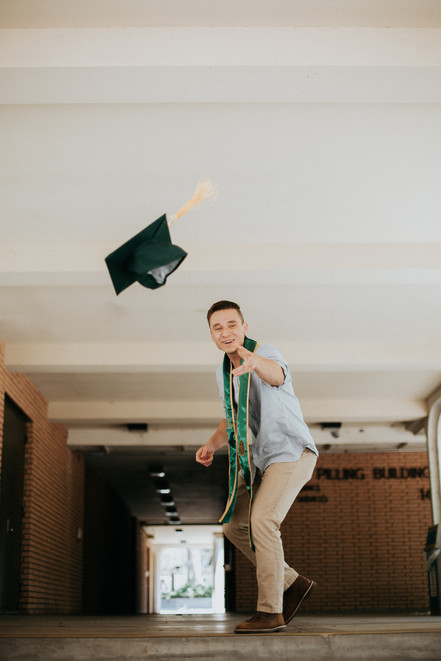 graduate standing on stairs in slacks and blue shirt throwing cap at the camera
