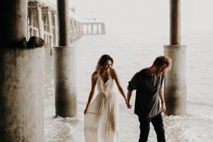 guy leading girl in cream dress by the hand under Malibu Pier