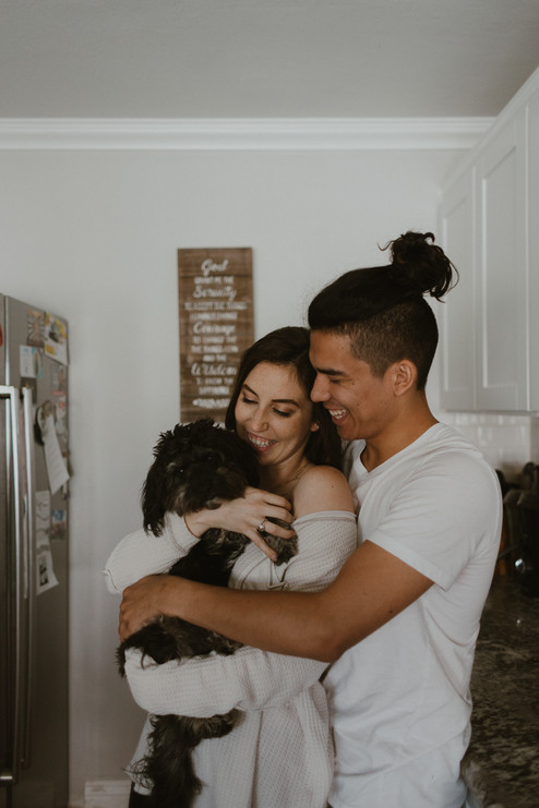 Couple wearing pajamas snuggling their dog in the kitchen