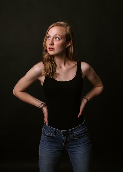 blonde female model with red lipstick and black tank top posing with her hands on her hips