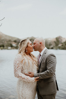 bride in white lace dress kissing groom in grey suit in front of lake