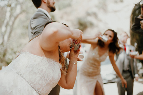 bride shotgunning a Coors Light with her wedding party