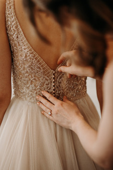 maid of honor buttoning up the back of bride's beaded wedding dress