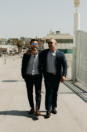 Groom laughing with his husband walking on the Hermosa Beach pier
