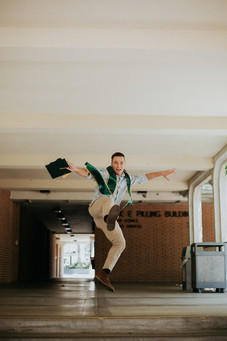 graduate in blue shirt and slacks holding cap and jumping in the air at Cal Poly San Luis Obispo