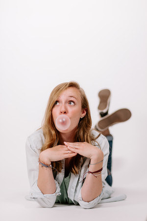young blonde woman in sneakers and jeans blowing bubblegum in a photo studio