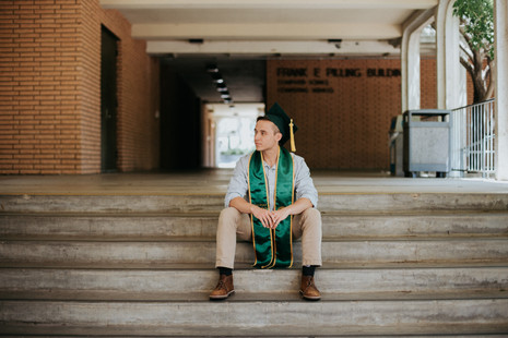 graduate in cap and gown sitting on stairs at Cal Poly San Luis Obispo